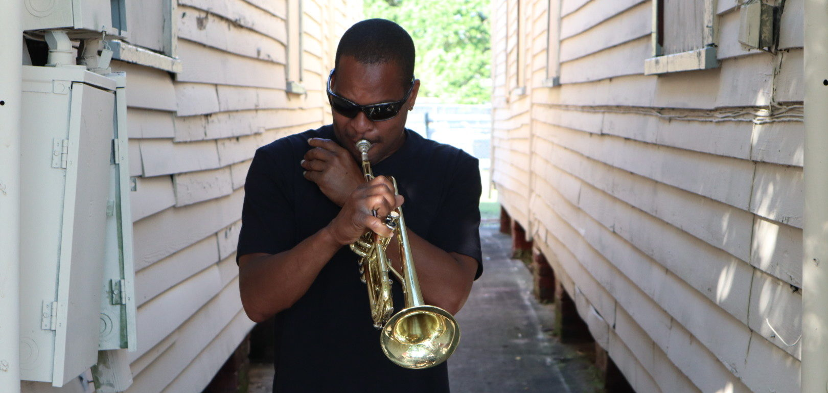 Derrick Shezbie, trumpeter of Rebirth Brass Band, practicing his trumpet on the side of Buddy Bolden's house.