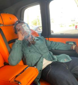 Curren$y smoking in a Rolls Royce
